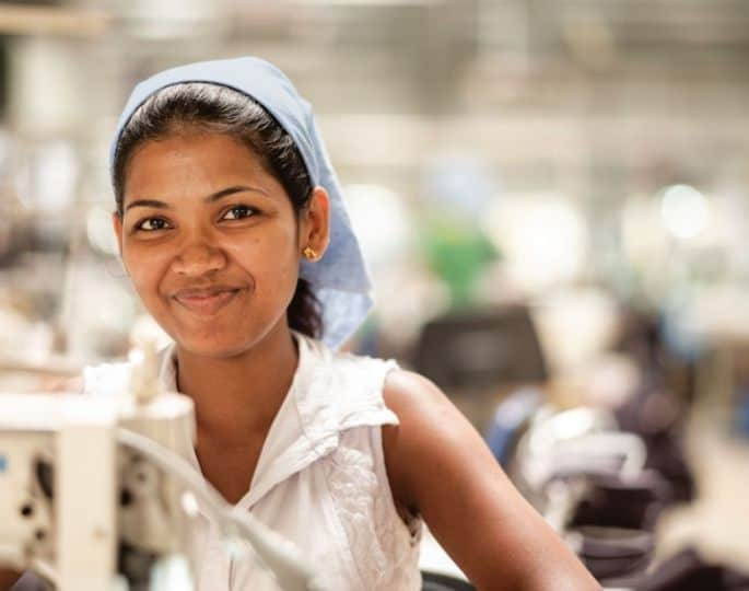 Woman working in a Patagonia clothing factory and smiling