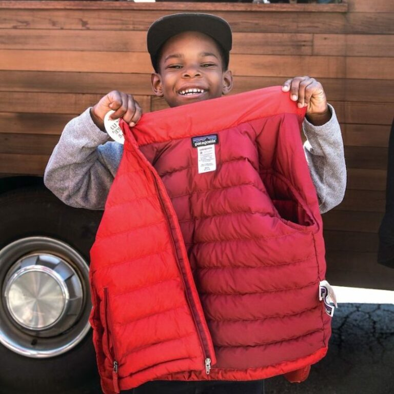 Young boy happily holding his repaired Patagonia red coat