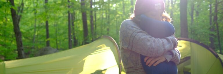 Woman hugging her camping pillow nearby her tent in the forest