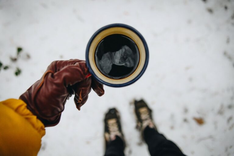 Main tenant une tasse à café de camping vue de haut