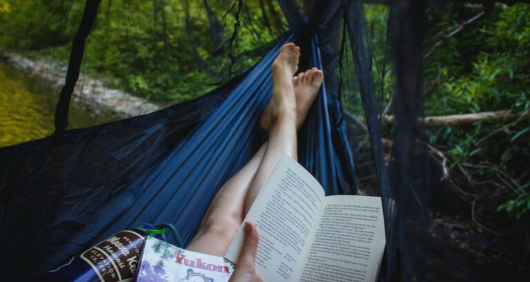 First person view of someone reading in a hammock